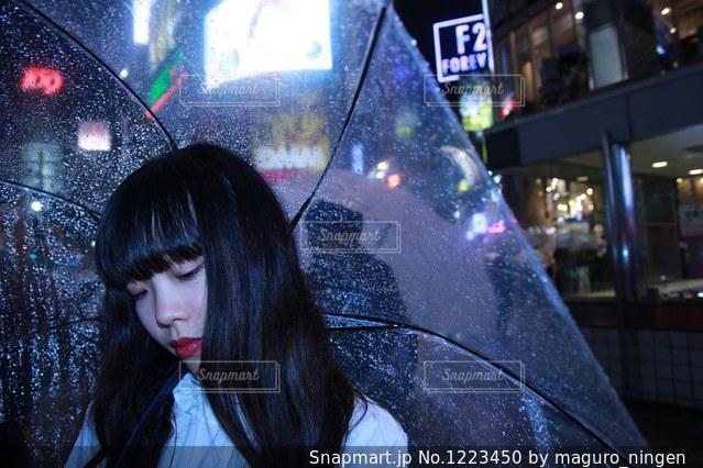 傘を持って雨の中に立っている人の写真・画像素材[1223450]