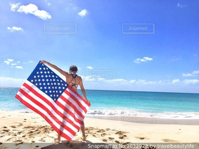 白砂のビーチに立っている人の写真・画像素材[1032928]