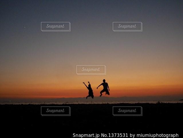 日没の前に立っている人のカップルの写真・画像素材[1373531]