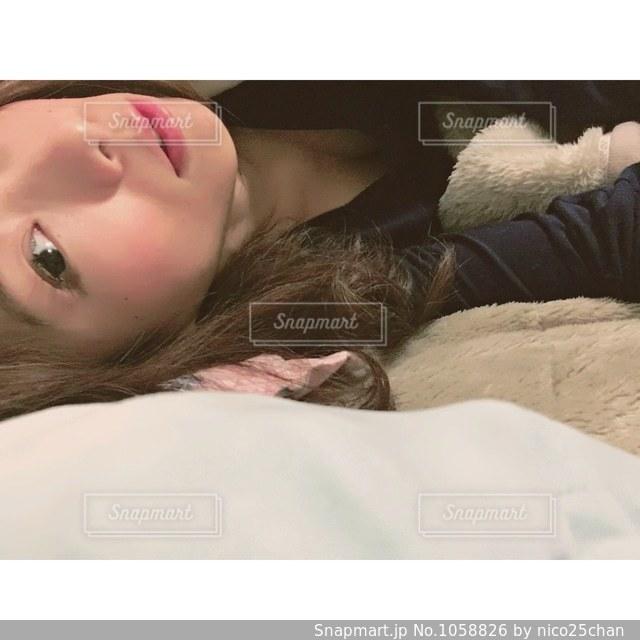 ベッドの上で横になっている人の写真・画像素材[1058826]
