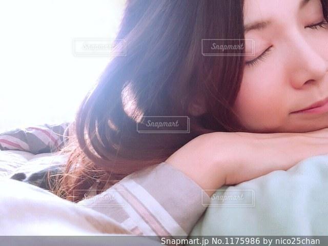 ベッドの上で目を閉じている女性の写真・画像素材[1175986]