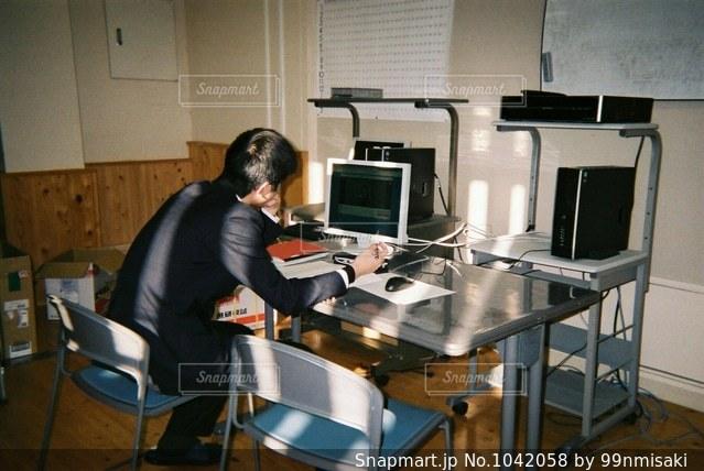 コンピューターの前で机に座っている人の写真・画像素材[1042058]