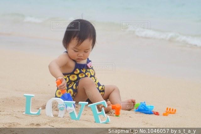 ビーチに座っている小さな子供の写真・画像素材[1046057]