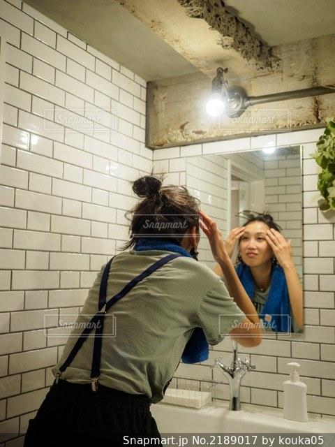 洗面所で鏡を見ながら顔をマッサージする女性の写真・画像素材[2189017]