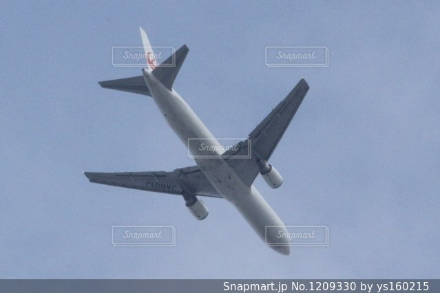 曇りの青い空を飛んでいるジェット大型旅客機の写真・画像素材[1209330]