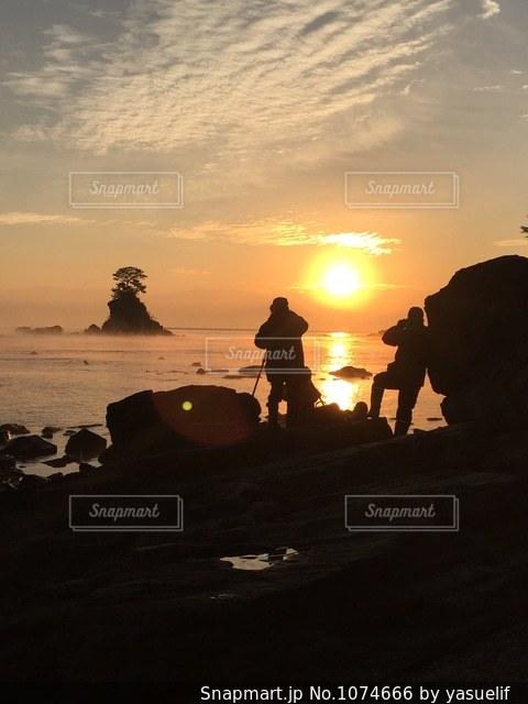 夕焼けの海を撮影する人の写真・画像素材[1074666]