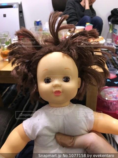 ぬいぐるみの上に座っている人形の写真・画像素材[1077158]