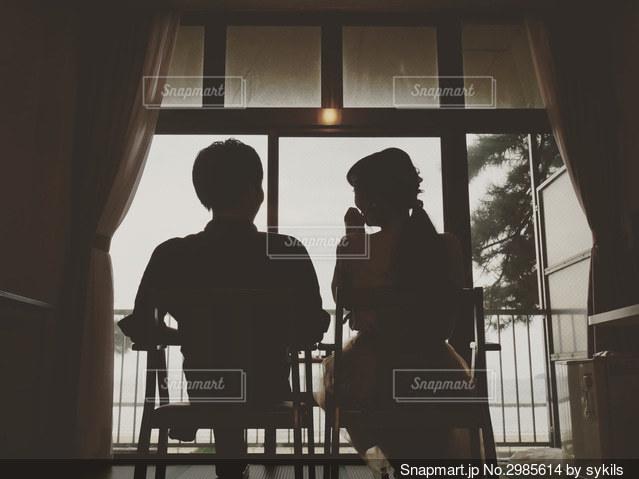 窓の前に座るカップルの写真・画像素材[2985614]