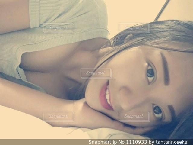 ベッドの上で横になっている人の写真・画像素材[1110933]