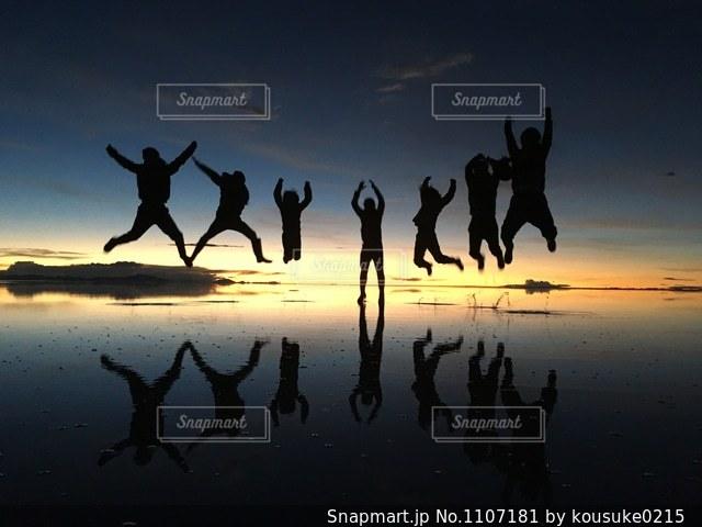 水の体の横に立っている人のグループの写真・画像素材[1107181]
