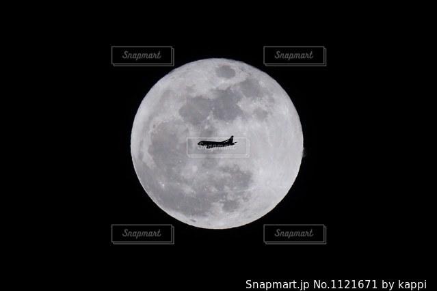 満月の前を通過する飛行機をパチリの写真・画像素材[1121671]