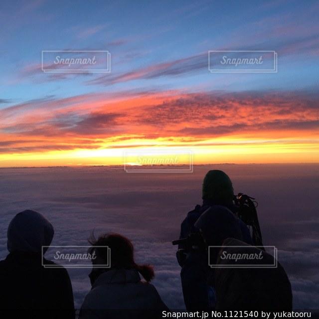 日没の前に立っている人々 のグループの写真・画像素材[1121540]