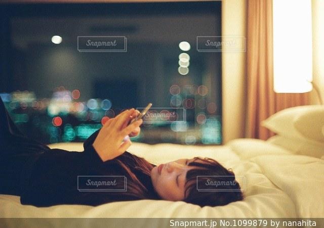 ベッドの上で横になっている人の写真・画像素材[1099879]