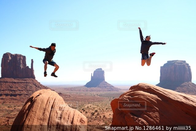 岩の上でジャンプしているカップルの写真・画像素材[1286461]