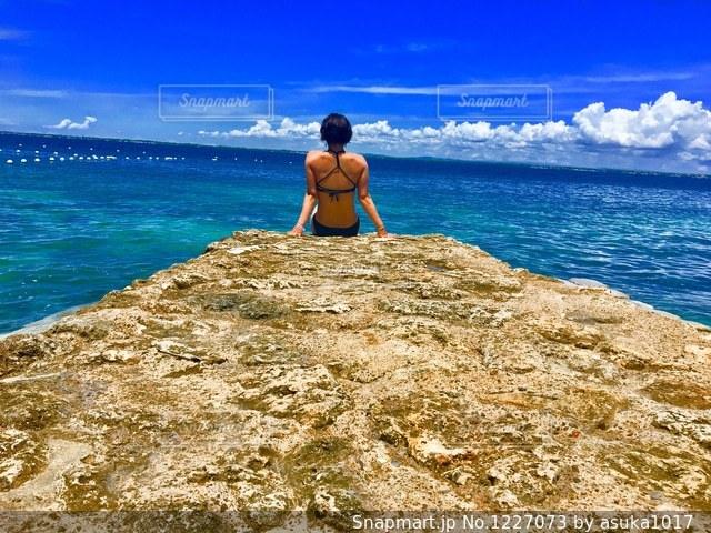 水の体の横にある岩のビーチに立っている人の写真・画像素材[1227073]