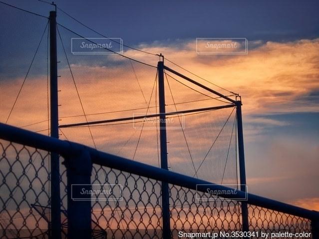フェンス越し放課後の夕暮れグラウンドの写真・画像素材[3530341]