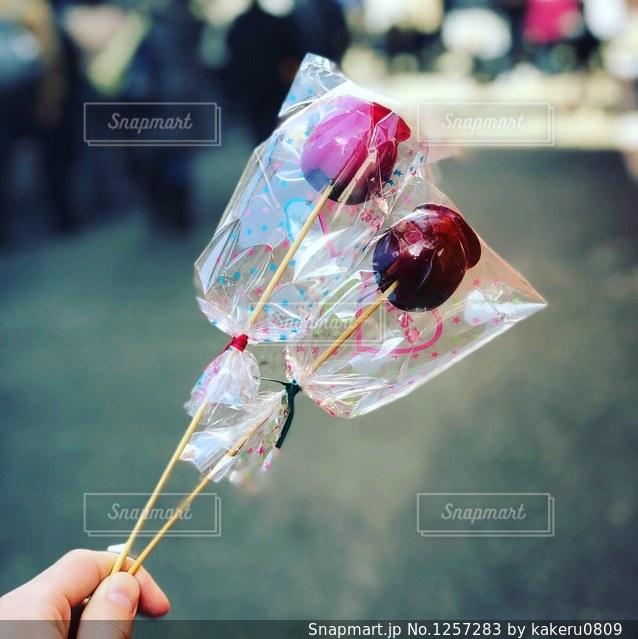 りんご飴を持っている人の写真・画像素材[1257283]