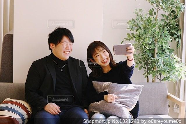 男とソファの上に座っている女性の写真・画像素材[1821241]