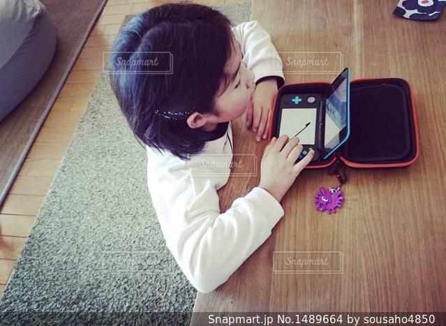 ラップトップを使用してテーブルに座っている少年の写真・画像素材[1489664]