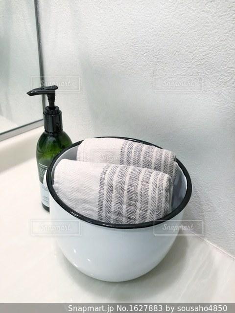 洗面所でホーローのボウルに収納されたタオルとハンドソープボトルの写真・画像素材[1627883]