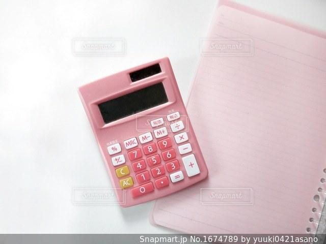 テーブルの上のピンクの携帯電話の写真・画像素材[1674789]