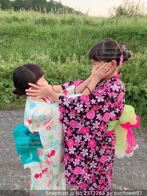 草の上に立っている小さな女の子の写真・画像素材[2371263]