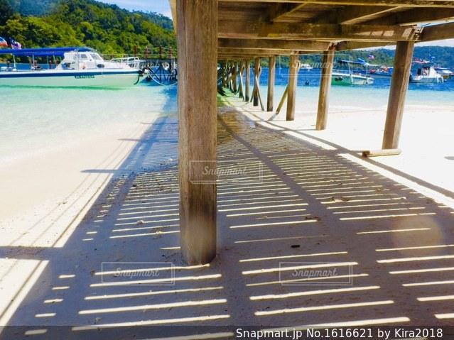 水の体の横に木製の桟橋の写真・画像素材[1616621]