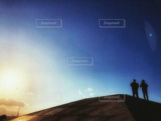 夕日を背景にした人の写真・画像素材[2858540]