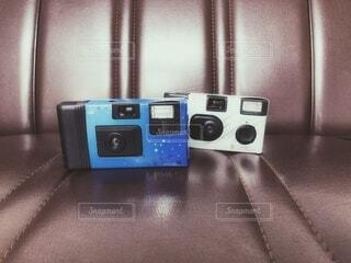 レトロ調ソファの上の二つのカメラの写真・画像素材[4775159]