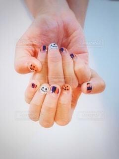 ハロウィン模様のジェルネイルの女性の手のアップの写真・画像素材[4899701]
