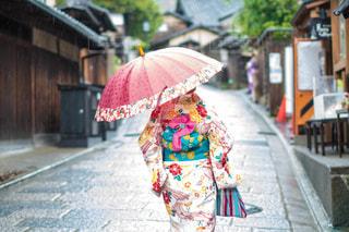 ピンクの傘を持って通りを歩いて女性の写真・画像素材[1744477]