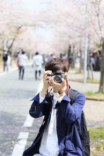 桜を背景に一眼レフカメラを構える男性の写真・画像素材[1867549]