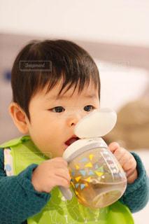 ストローマグでお茶を飲む赤ちゃんの写真・画像素材[2085335]