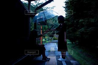 傘を持って雨の中に立っている男の人の写真・画像素材[819969]