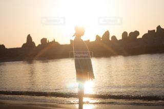 水の体の横に立っている人の写真・画像素材[923571]