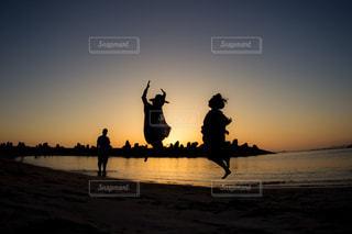 ビーチでの背景の夕日に人々 のグループの写真・画像素材[956851]