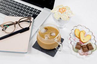 コーヒー カップの横にあるテーブルの上に座っているケーキの写真・画像素材[1266450]