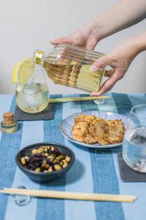 テーブルに食べ物のプレートを保持している女性の写真・画像素材[1281611]