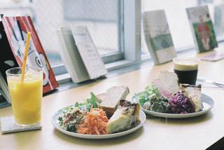 食品のプレートをテーブルに着席した人の写真・画像素材[1287455]