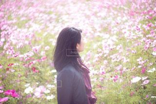 花の前に立っている女性の写真・画像素材[1585393]
