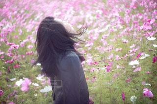花の前に立っている人の写真・画像素材[1585397]