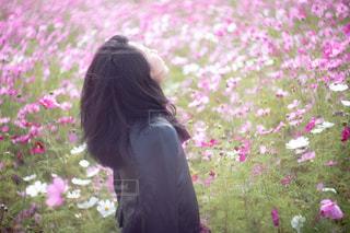 花の前に立っている人の写真・画像素材[1585400]