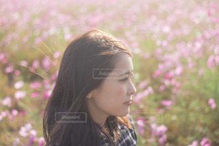 ピンクの花を身に着けている女性の写真・画像素材[1588894]