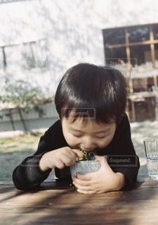 テーブルの上に座って若い男の子の写真・画像素材[1646321]