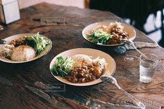 木製のテーブルの上に座っている食べ物の皿の写真・画像素材[2743240]