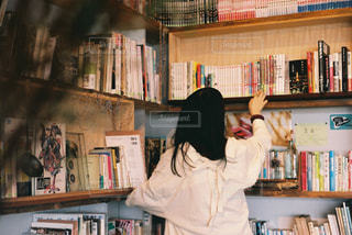 本棚の前に立っている人の写真・画像素材[2894331]
