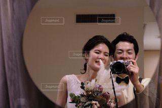 カメラに向かってポーズをとる鏡の前に立つ人の写真・画像素材[2691963]