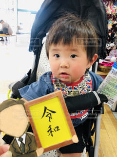 テーブルの上に座っている小さな男の子の写真・画像素材[2113794]