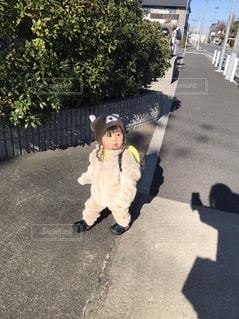 スケートボードに乗って道路の脇に乗っている少年の写真・画像素材[2852762]