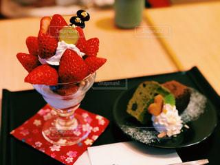 木製テーブルの上にフルーツとケーキの写真・画像素材[1764876]
